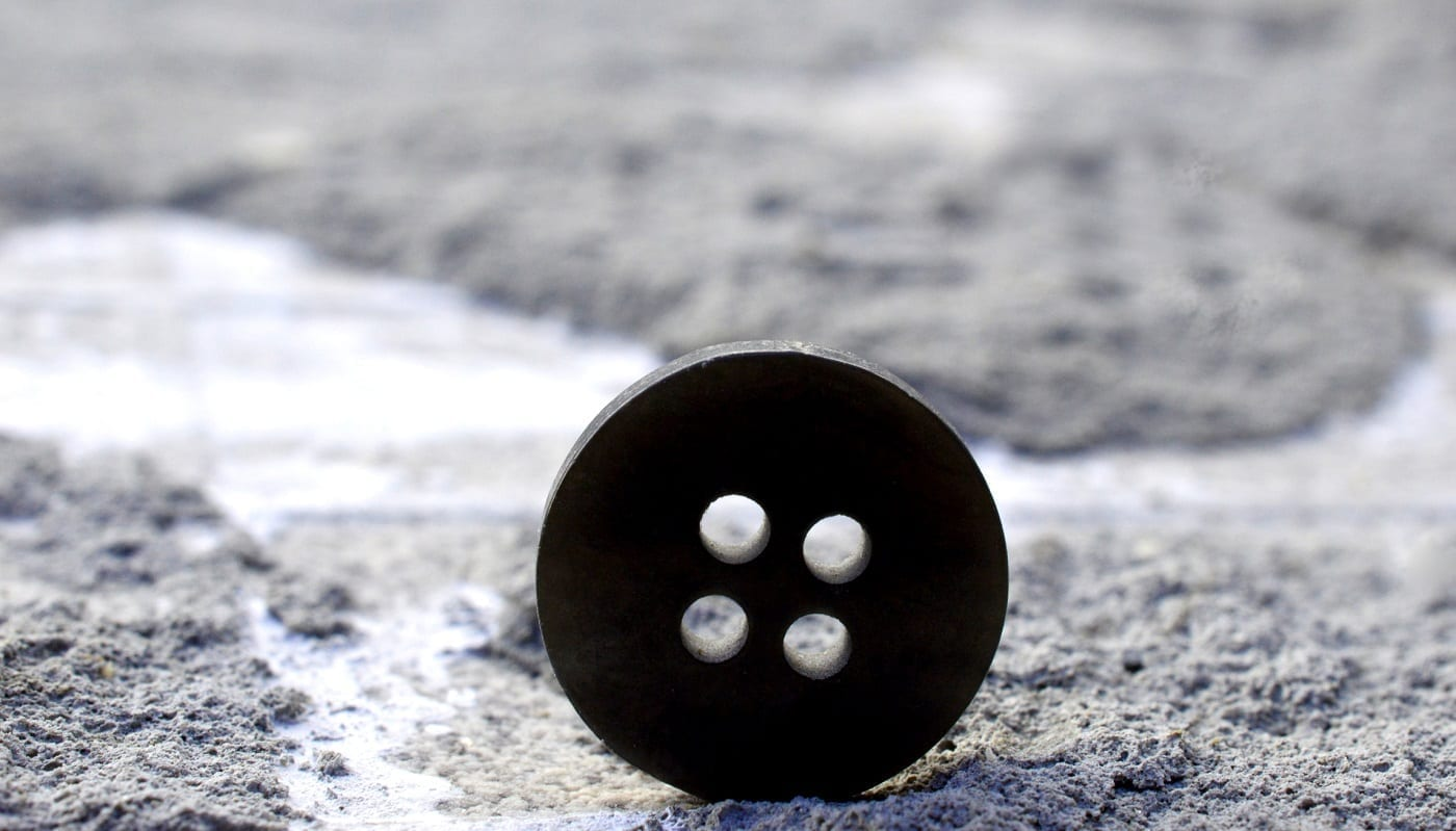 Sewing button on the ground: ID 128601237 © Nehru | Dreamstime.com