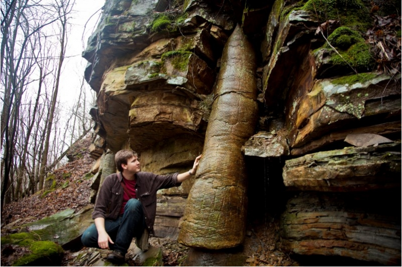 David Rives standing by a tree fossil extending through many layers of rock