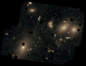 This deep image of the Virgo Cluster obtained by Chris Mihos and his colleagues using the Burrell Schmidt telescope shows the diffuse light between the galaxies belonging to the cluster. North is up, east to the left. The dark spots indicate where bright foreground stars were removed from the image. Messier 87 is the largest galaxy in the picture (lower left).