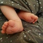 Baby feet on a gray blanket