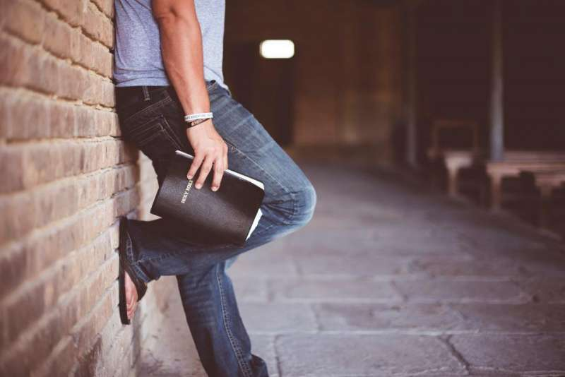 Lower part of a man holding a Bible and leaning against a brick wall