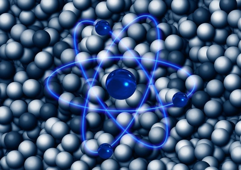 Atom graphic with spherical depictions in the background, photo credit: Pixabay
