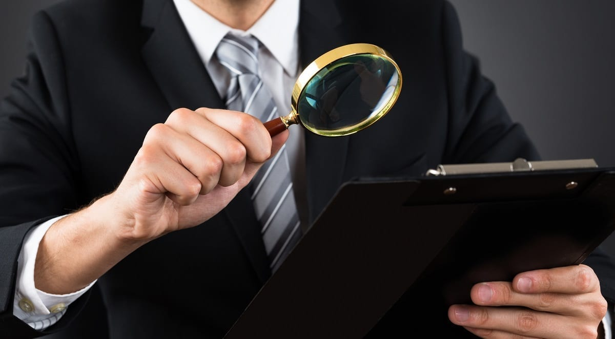 Inspecting a document with a magnifying glass: ID 77509910 © Andrey Popov | Dreamstime.com