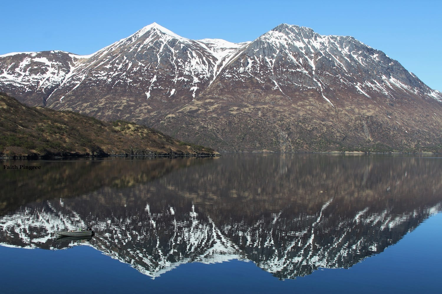 Snow dusted mountains with lake reflections