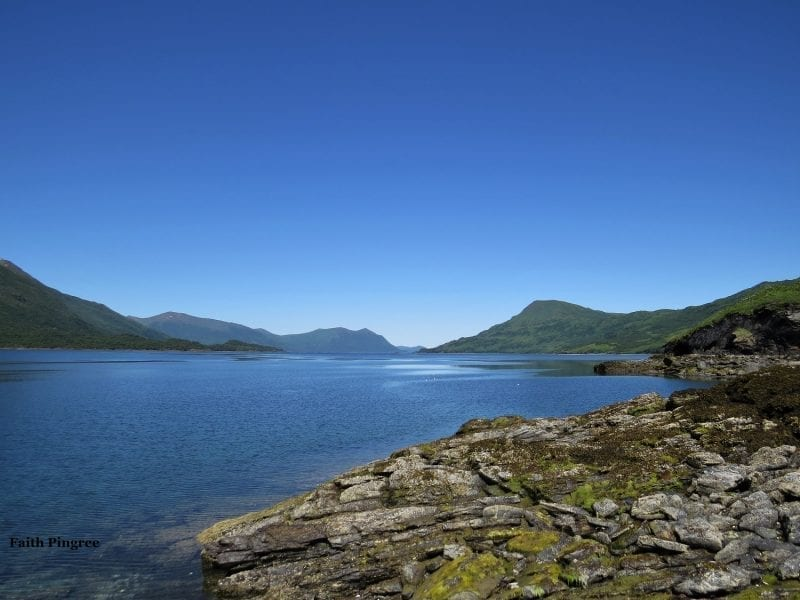 Alaskan bay with rocky shore and distant mountains, photo credit Faith P.