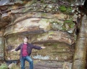 David Rives standing between two insitu polystrate tree trunks