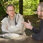 Two men with an open Bible outdoors, one is skeptically listening to the other: Photo 1302675 © Kenneth Sponsler - Dreamstime.com