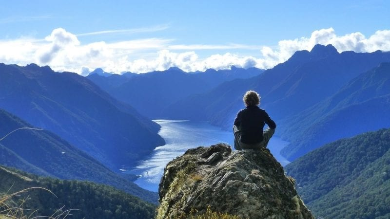 Man sitting at the summit of a hike overlooking Kepler Bay NZ: Image by Gerralt van Soest from Pixabay