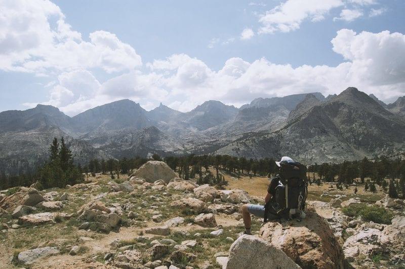 Hiker watching rock desert with hazy mountains, photo credit: Pixabay