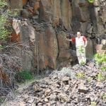 Lava rock face with a man showing scale, photo credit: Ian Juby