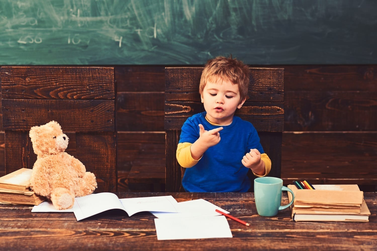 Small child counting on fingers surrounded by college-style setting and Teddy Bear: ID 139764622 © Volodymyr Tverdokhlib | Dreamstime.com