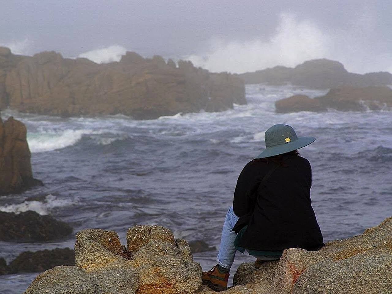Woman in hat overlooking a rainy sea, photo credit: Pixnio