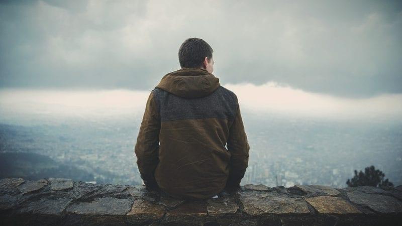 Man sitting on summit overlooking cloudy terrain, photo credit: Pxhere
