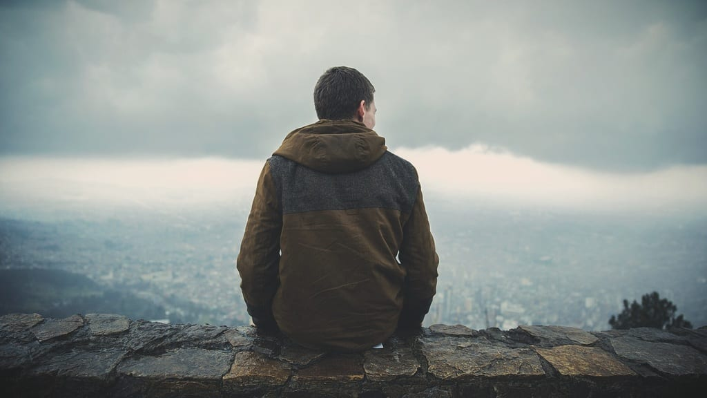 Man sitting on summit overlooking cloudy terrain, photo credit: Pxhere