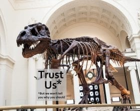 Sue the T.rex holding a 'sign' saying Trust Us, but we won't tell you why you should, adapted from: ID 27396520 © Cmlndm | Dreamstime.com