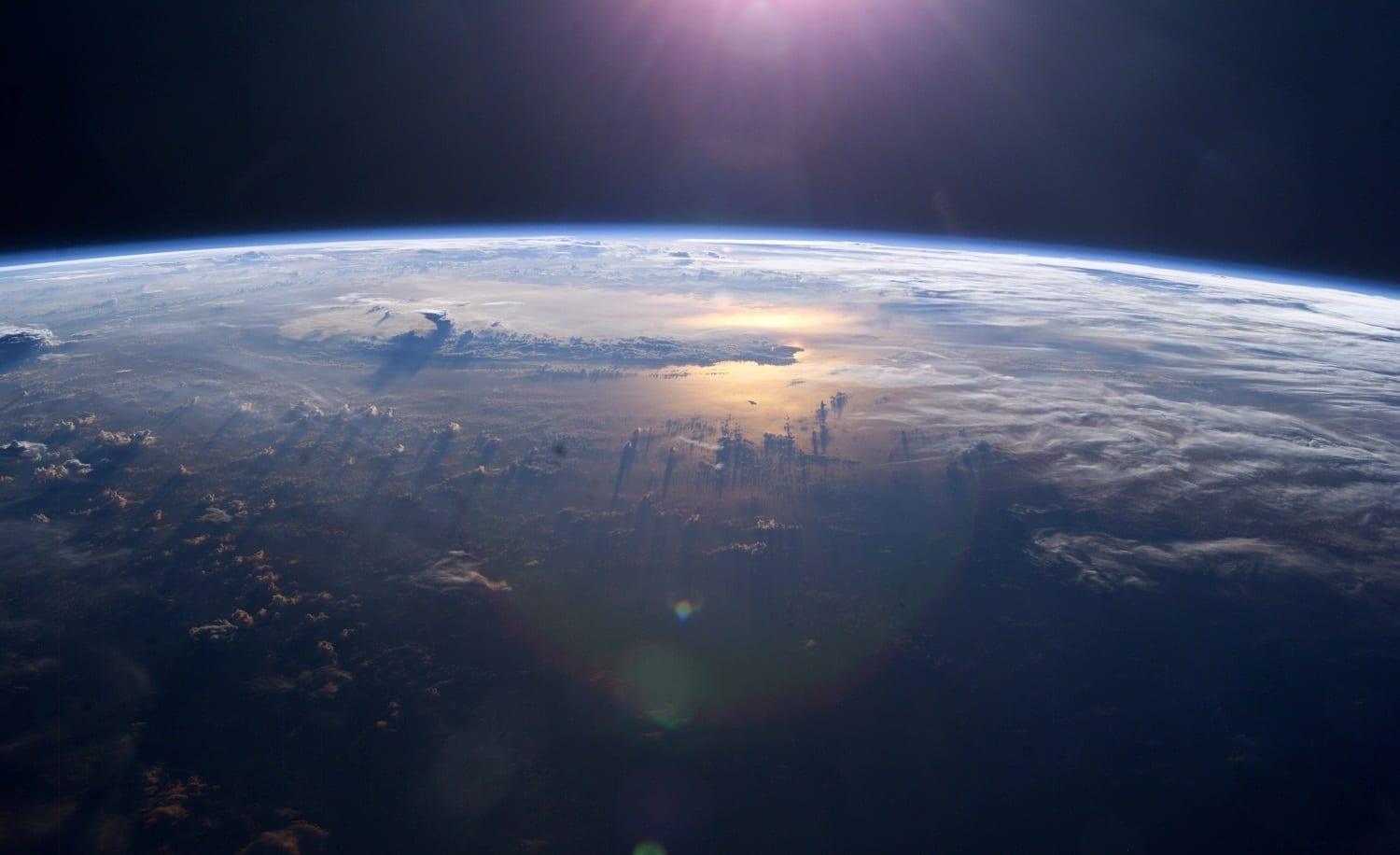 Earth from above showing thunderheads above the ocean reflecting sunlight, photo credit: NASA