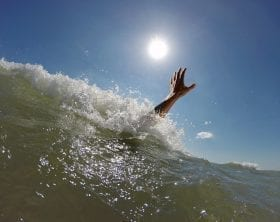 Drowning person's arm coming up out of a wave: Photo 76671162 © Mike_kiev - Dreamstime.com