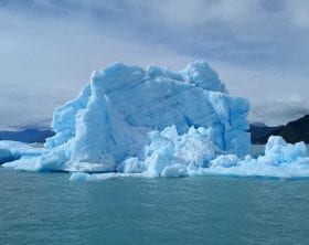 Blue-tinged iceberg with mountains in backdrop, photo credit: Pxhere