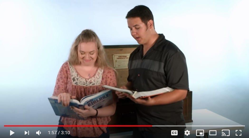 High School students examining biology textbooks, photo credit: Genesis Apologetics
