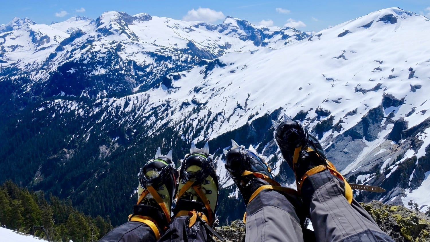 Crampone-clad feet in front of a view of snow covered North Cascade Mountains: Photo 73296343 © Aquamarine4 | Dreamstime.com