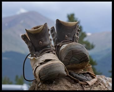worn hiking boots with mountain in the background, photo credit: Pat Mingarelli