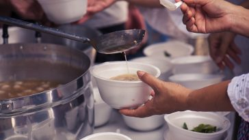 Hands passing out bowls of soup to the homeless: Photo 118467980 / Feeding Homeless © Todsaporn Bunmuen | Dreamstime.com