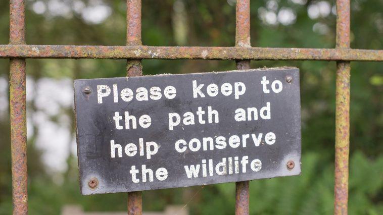 Please keep to the path sign on a rusty fence: Photo 97411565 © Richard Stemp | Dreamstime.com